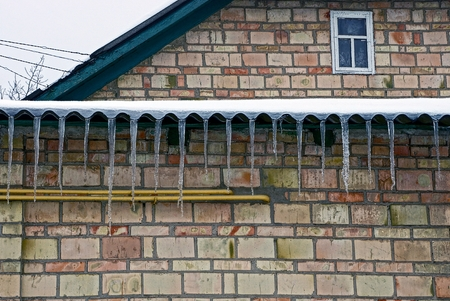 row of icicles from a roof on a brick wall at home