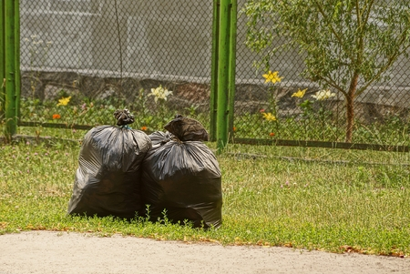 Closed garbage bags with garbage on the lawn Stock Photo - 98165084