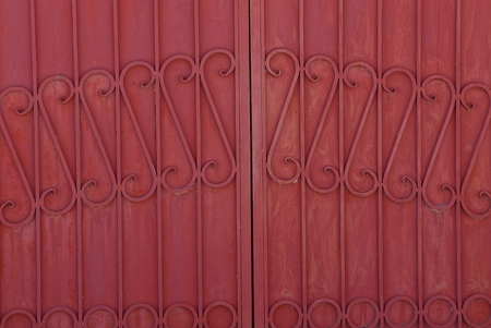 iron background from a steel forged pattern on a red metal fence