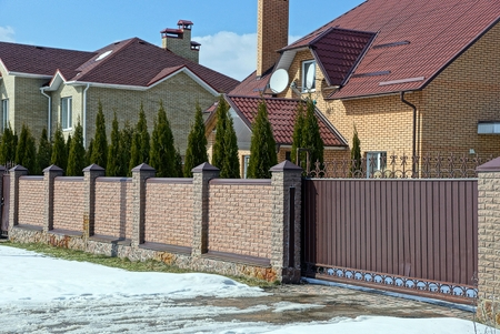 Brown brick fence and iron closed gates on the street near the road in the snow