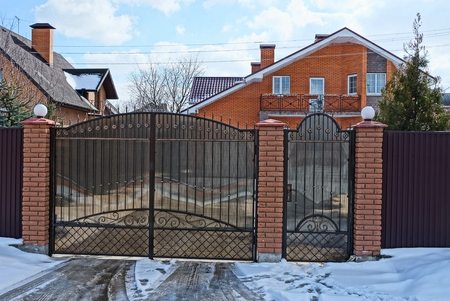 closed brown gates and part of the fence in the street near the road in the snow