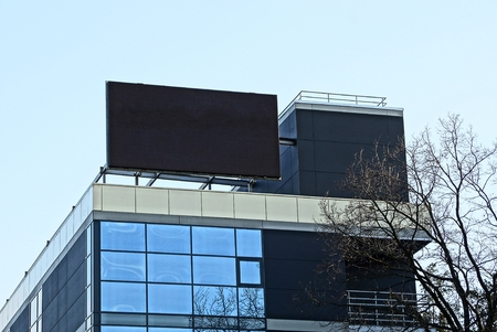 big black screen on the roof of a tall house with windows on the sky background Stock Photo