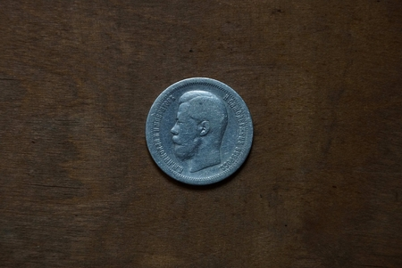 old silver russian coin on a wooden board