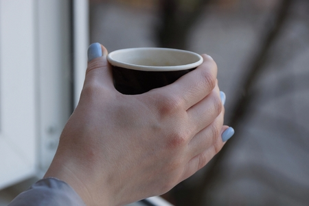 paper cup with coffee in hand girl Imagens