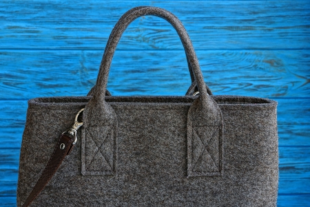 A large closed gray bag made of cloth on a blue wooden table