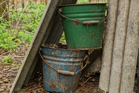 two old dirty buckets in the garden Stockfoto