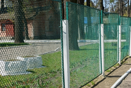 part of an iron fence made of green mesh on the street