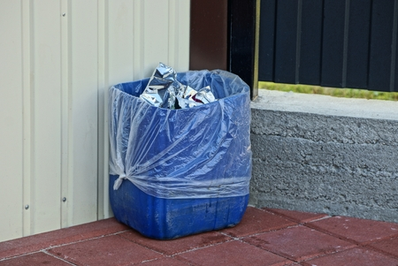 blue plastic urn with garbage at the wall