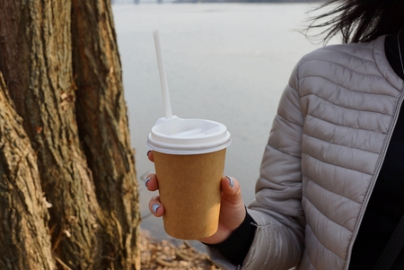 brown paper glass with drink in the hand of a girl on the street