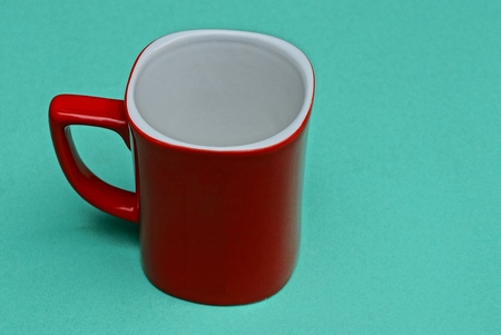 a large red empty cup is on a green table Imagens