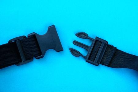 Mousqueton en plastique noir ouvert sur fond bleu Banque d'images