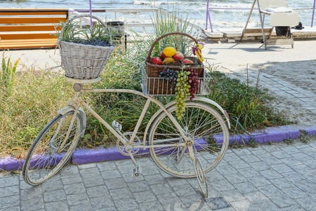 white old bicycle with baskets of fruit and vegetation stands on the sidewalk near the sea