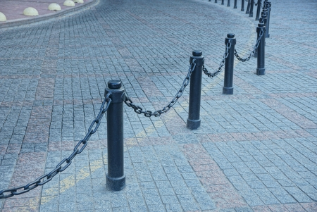 Black railing from iron chains and stones on a gray pavement of stones Banque d'images