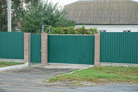 The green gate of the metal and the fence in the street