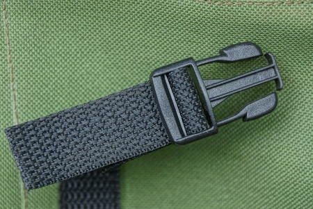 one black plastic carbine on a green fabric backpack