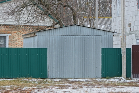 gray iron garage and green metal fence Imagens