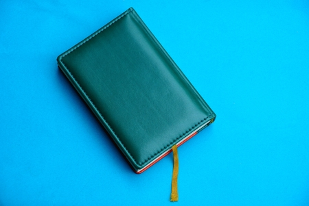 green notepad with leather cover on a blue background Stock Photo