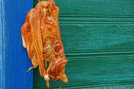 brown smoked chicken hanging on a blue green wall