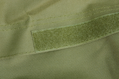 green fabric texture on a sticky buckle on a backpack Stock Photo
