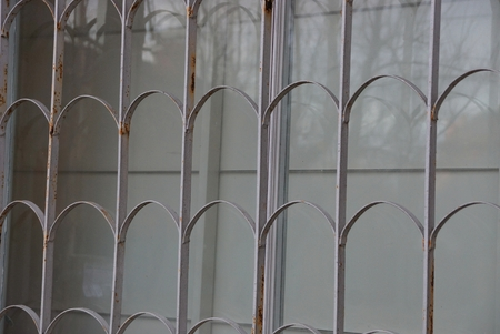 gray metal texture of iron bars on a glass window