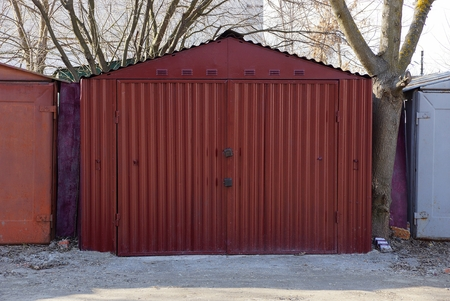 large red metal garage with closed gates standing outside