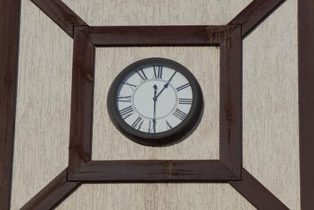 big round clocks hang on a gray brown building wall Imagens