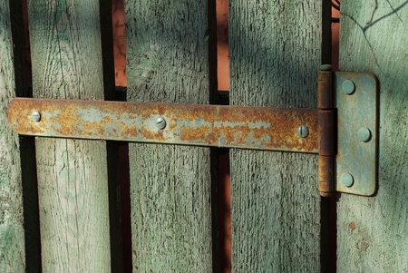 rusty hinge on green wooden fence boards Stock Photo