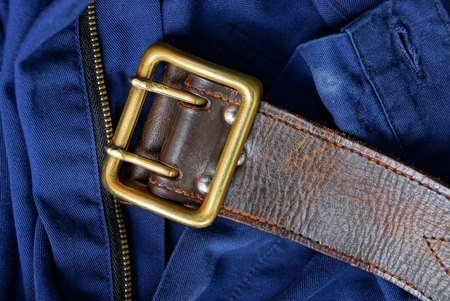old brown leather belt with brass buckle on blue pants