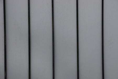 metal texture from a row of black bars on a gray wall