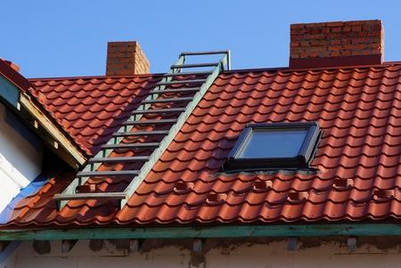 Techo de tejas rojas con ventana, escaleras y chimenea. Foto de archivo