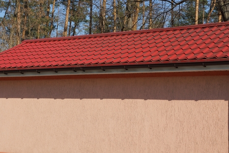 big wall of the house with a red tile roof