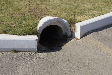 concrete sewer pipe on green lawn with green grass