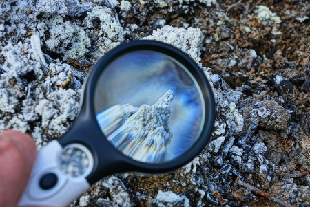 round magnifier increases gray white mineral on earth Stock Photo