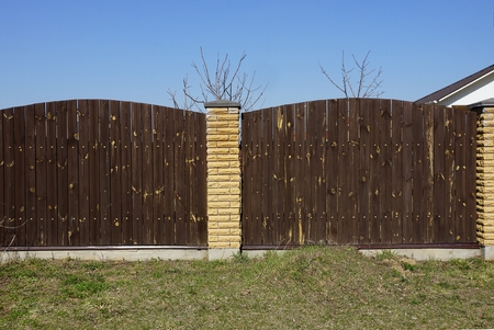 brown fence of wood against the blue sky