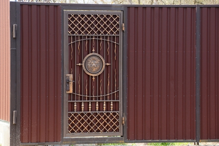 brown gate and metal fence Banco de Imagens