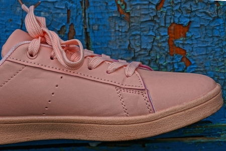 one pink leather sneaker on the blue board