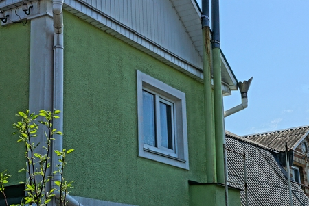 one white window on the green plastered wall of a private house