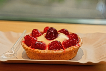 red tartlet cake with red strawberries on a gray paper tray with a small spoon