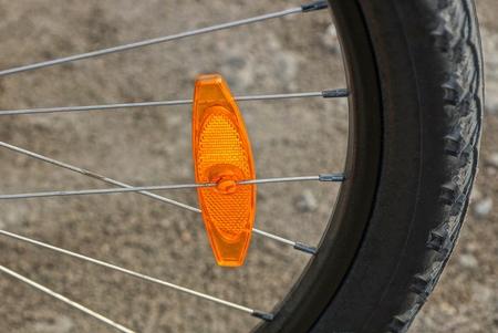 ein oranger Kunststoffreflektor am Rad