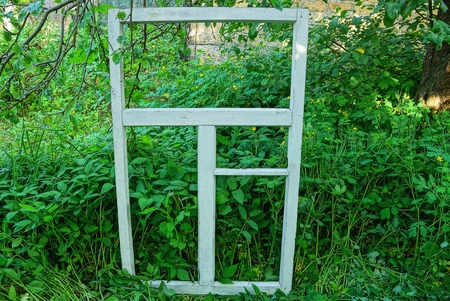 old white wooden window frame stands in green Stock Photo