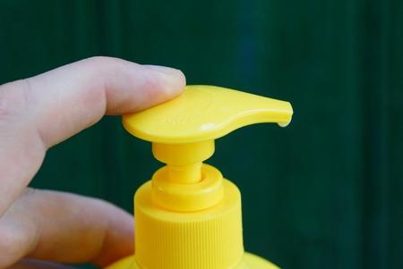 finger clicks on a yellow plastic dispenser Фото со стока