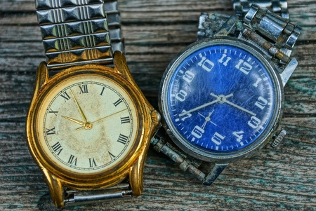 yellow and blue old shabby watch with a metal strap on a gray table
