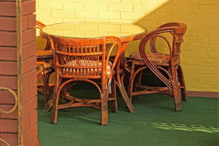 brown table chairs against a brick wall Imagens
