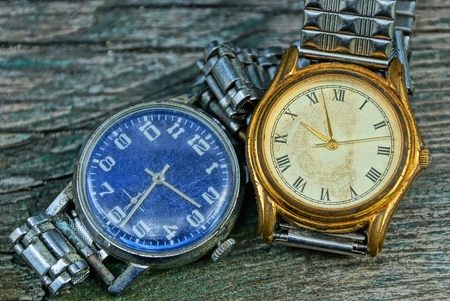 two yellow and blue shabby watch with a metal strap on a gray table Stock Photo - 124986580