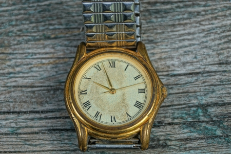 one yellow old shabby watch with a metal strap on a gray table Stock Photo