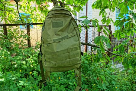 one large military backpack hanging in green
