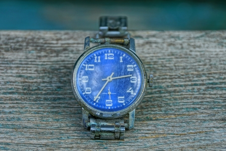 blue old shabby watch with a metal strap on a gray table Stock Photo