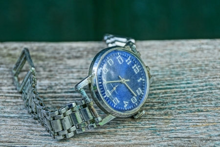 one blue old shabby watch with a metal strap on a gray table
