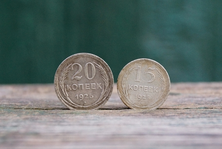 two old silver coins stand on a gray table