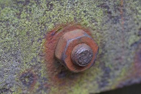 old nut on a rusty bolt on a green iron wall Фото со стока